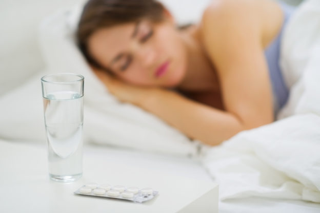 Closeup on pills and glass of water on table and sleeping woman in background